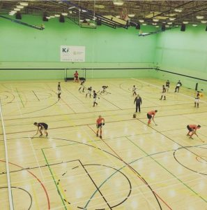 Students playing indoor hockey